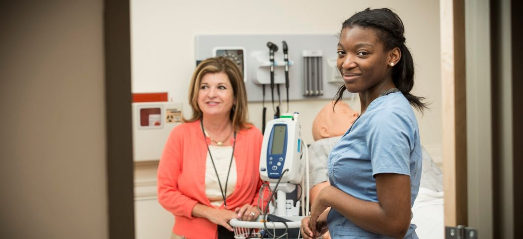 image of a young woman in nursing scrubs looking at camera with another healthcare worker